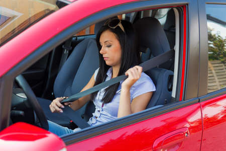 vehicle seat: young woman strapped to the seat belt in a car Stock Photo