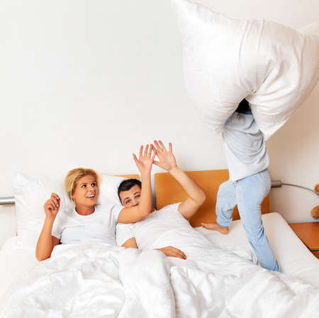 happier: a young family lying in bed in the bedroom
