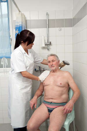 a senior is bathed by nurses photo