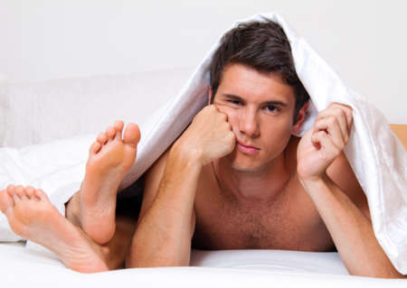 impotence: a young couple in bed has problems and crisis  divorce and separation