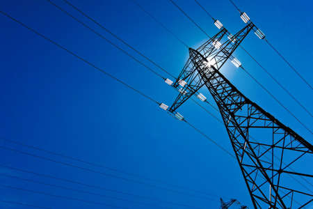 the utility pole of a high voltage line with sun and blue sky  energy supply by power line  photo