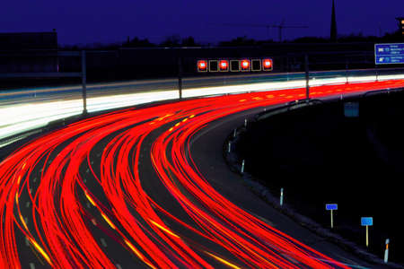road conditions: many cars are driving at night on a highway and create light trails