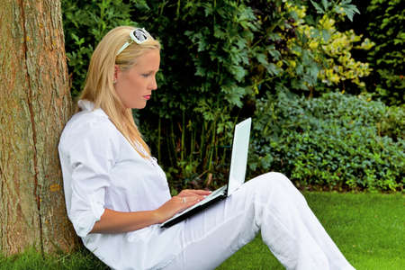 edv: a young woman sitting with a laptop computer in the garden and surfs the internet    Stock Photo