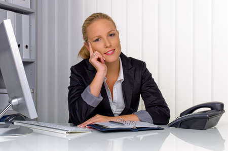 a young, successful business woman sitting at her desk in the office Stock Photo - 15652275