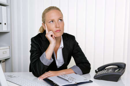 a pensive businesswoman sitting at her desk in an office photo
