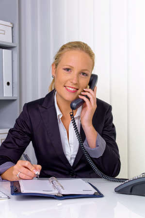 a friendly woman telephoned at her desk in the office and recorded events in the calendar photo