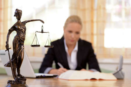 a young lawyer is sitting at her desk in the office Stock Photo - 15652277