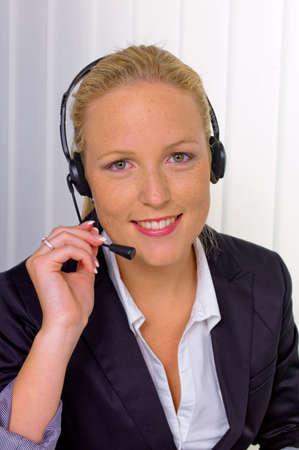 een vriendelijke jonge vrouw met hoofdtelefoon in de klantenservice aan de telefoon met een klantvriendelijke Sales Associate Stockfoto