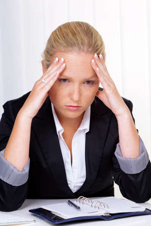 tenseness: a young woman with migraine headaches and sitting in an office