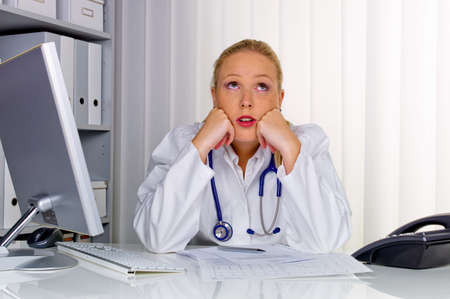 doctor burnout: a young female doctor with stethoscope in her doctor s office