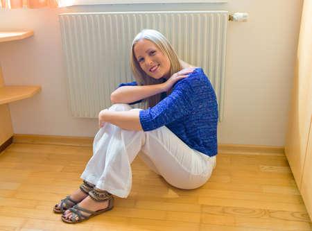 ordenanza: una mujer joven se sienta delante de un radiador en invierno Foto de archivo