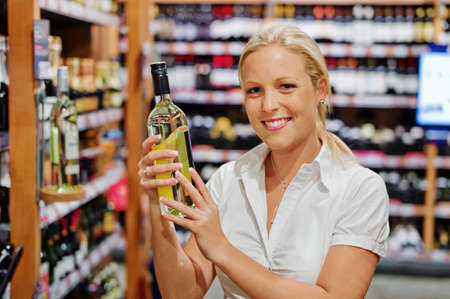 local supply: a woman buys wine in a supermarket  wine shelf with wines from around the world  Stock Photo