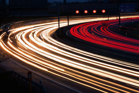 toll: many cars are driving at night on a highway and create light trails