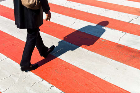 a woman walks on a pedestrian crossing  shadows on a protection path