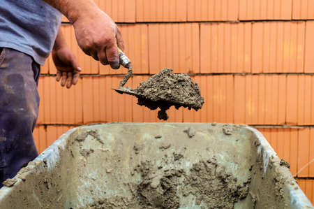 neighborly: construction worker with trowel on walls of a shell in solid construction  representative photo of the black economy and community care Stock Photo