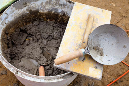 neighborly: bucket of mortar at the construction site of a detached house Stock Photo