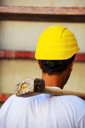a construction worker with yellow helmet on a construction site carries a hammer Stock Photo