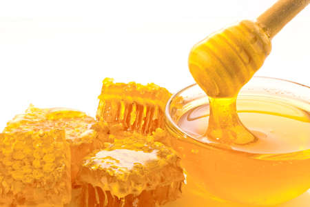 a spoon is kept in a pot of honey. isolated against white background photo