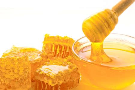 abejas panal: una cuchara se guarda en un tarro de miel. aislado contra el fondo blanco