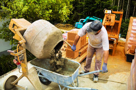 peoplesoft: the construction workers on the construction site of a house  mixing mortar for bricklaying  house building and neighborhood