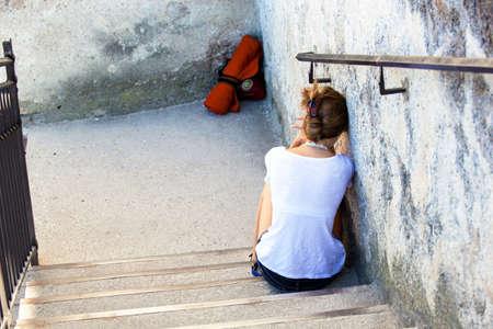 psique: una mujer joven que se sienta triste y solitario en una escalera
