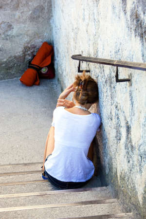 discouraged: a young woman sitting sad and lonely on a staircase  Stock Photo