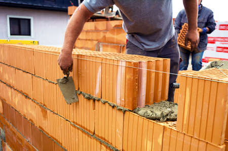 bricklayer: trabajadores de la construcci�n en las paredes de una concha s�lida pared de ladrillo en la construcci�n de una vivienda unifamiliar Foto de archivo