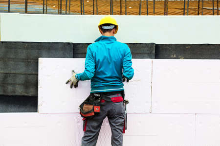 house renovation: construction workers at a construction site when the building insulation Stock Photo
