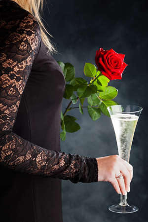 a woman in evening dress with a red rose and a glass of sparkling wine or champagne photo