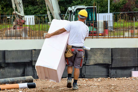 work worker workforce world: a construction worker with insulation at the construction site of an industrial building Stock Photo