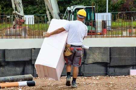 illicit: un operaio edile con isolamento nel cantiere di un edificio industriale