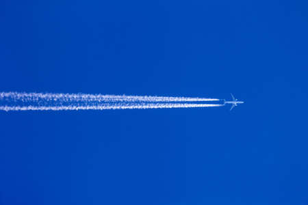 a plane with contrails against a blue sky. holiday travel and air pollution Stock Photo - 16151558