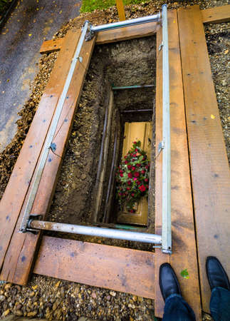 the open coffin with fresh grave in a cemetery  after the funeral photo