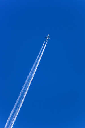 emission: a plane with contrails in the blue sky  smog and air pollution