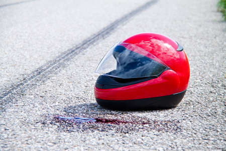 emergency braking: motorcycle helmet with some blood stains on the road