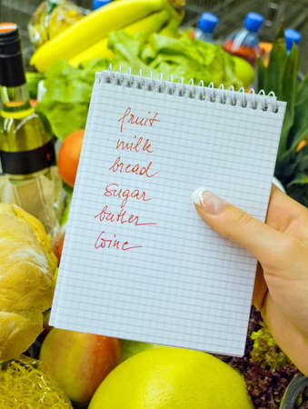 a woman holding a shopping list in a supermarket in the hand  english language Stock Photo - 16357348