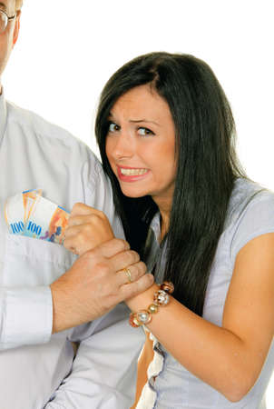 births: young woman pulls money out of mans pocket Stock Photo