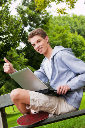 ordinateur: a teenager with laptop outdoors  sitting in the park mobile internet Stock Photo
