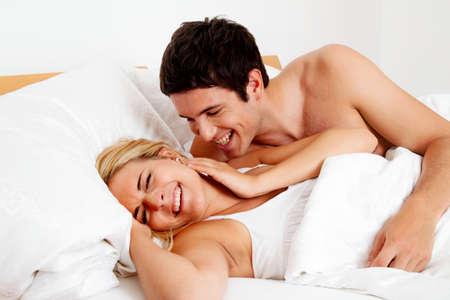 deseo sexual: pareja se divierte en la cama risa, la alegr�a y el erotismo en el dormitorio