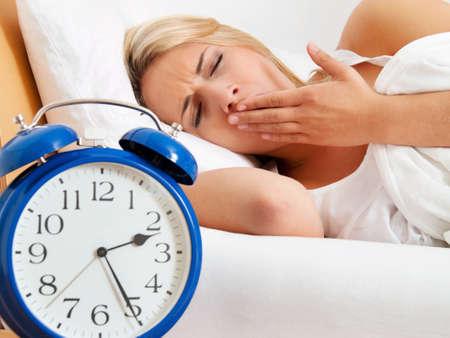 insomnio: insomnio con el reloj en la noche la mujer no puede dormir