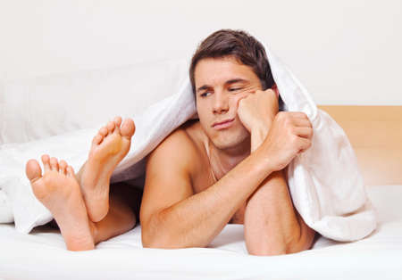 potency: a young couple in bed has problems and crisis