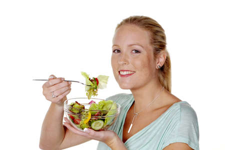 healthier: a young woman eating a fresh salad at lunch  healthy diet with vitamins