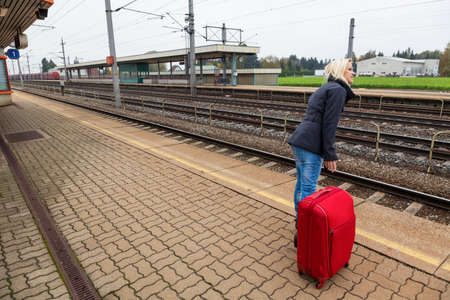 a young woman with luggage waiting on the platform of a railway station for their train  train delays