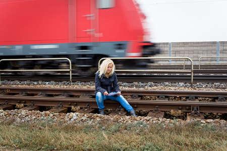 the farewell: una mujer joven con pensamientos suicidas que se sientan en una pista considera nota de suicidio en la mano y piensa en el suicidio