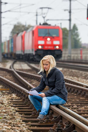 a young woman with suicidal thoughts sitting on a track  considers suicide note in his hand and thinks about her suicide  photo