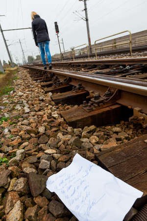 a young woman leaves a suicide note and goes to commit suicide on a railway  letter in german photo