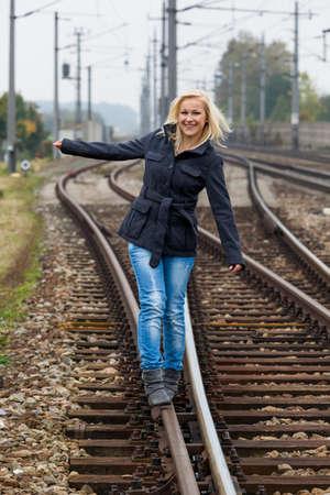 joie: auf der Suche nach der richtigen Entscheidung setzt eine junge Frau Balancieren auf einem Track Leben die Weichen