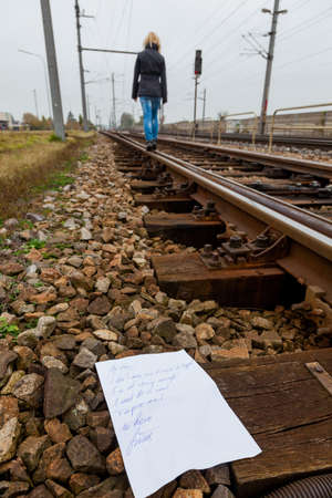 a young woman leaves a suicide note and goes to commit suicide on a railway  letter in english Stock Photo - 16469498