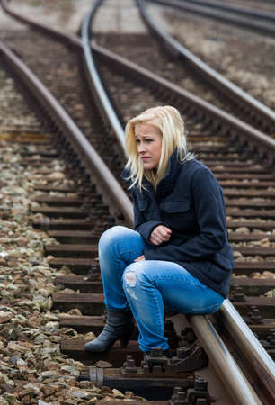 existential: a young woman is sad, anxious and depressed  sitting on a track and is lonely Stock Photo