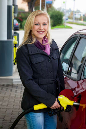 motorist: a young woman at a gas station gasoline tank  the cost of the car because of the gas prices are getting more expensive
